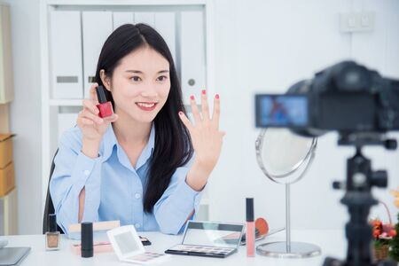 Photo for Beautiful asian girl talking about her nail polish color in front of camera to recording vlog video live streaming at her shop. - Royalty Free Image