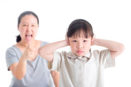 Foto de Displeased Girl covering her Ears from Scolded by her mother on white background - Imagen libre de derechos