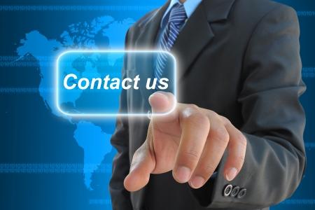 Foto de businessman hand pushing contact us button on a touch screen interface  - Imagen libre de derechos