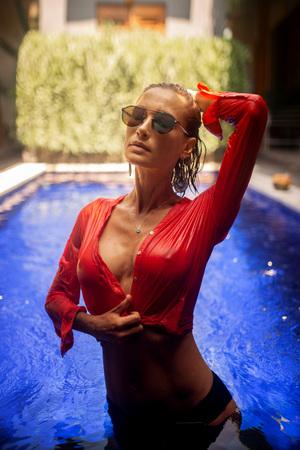 Foto de fashion photo of beautiful woman wth brunette hair in sexy transparent red blouse and mirror glasses posing in blue pool in Bali - Imagen libre de derechos