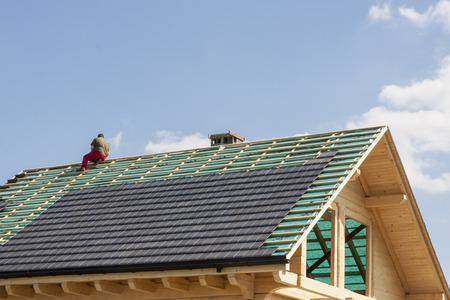 Photo pour Roofer working on the top of the unfinished roof - image libre de droit
