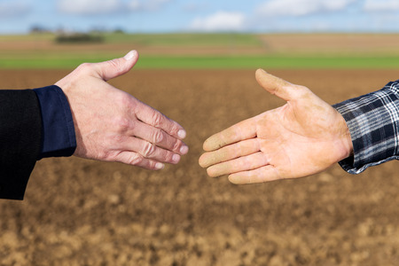 Foto de Close up Handshake between businessman and farmer - Imagen libre de derechos