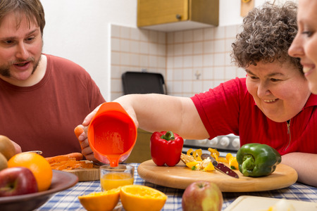 Foto de a mentally disabled woman and two caretakers cooking together - Imagen libre de derechos