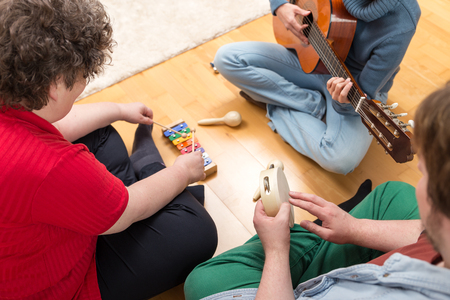 Photo pour three persons playing sundry instruments at home - image libre de droit