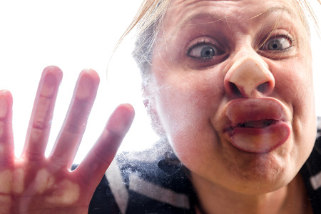 Photo for woman with fish mouth at the window makes a funny grimace - Royalty Free Image