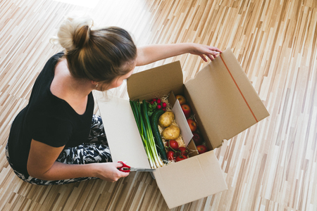 Photo pour woman opening a vegetable delivery box at home, online ordering - image libre de droit