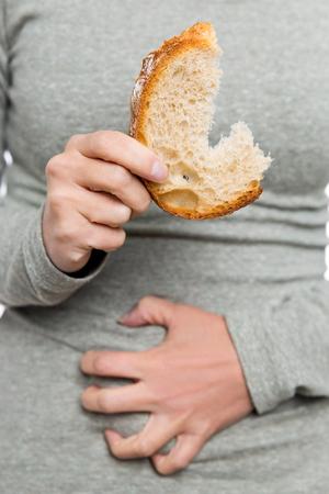 Foto de Woman holding wheat bread, celiac disease or coeliac condition, abdominal pain - Imagen libre de derechos