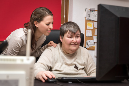 Photo pour caregiver and mentally disabled woman learning at the computer, special education - image libre de droit