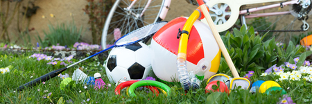 spring or summer with various outdoor fun equipment, green meadow with a bicycle