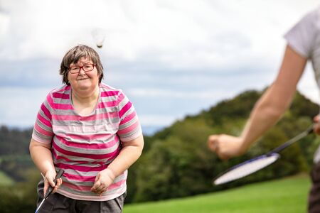 Foto de mental disabled woman is playing badminton to train her motor abilities, exercises with a friend or therapist outdoors on a meadow - Imagen libre de derechos