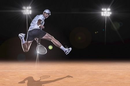 Tennis player jumping for the ball behind on tennis court