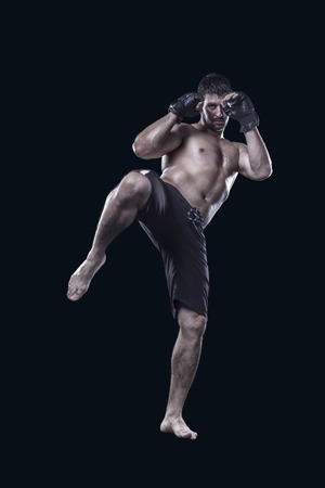 mma fighter hitting with knee isolated on black background