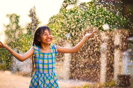 Happy little asian girl in the summer rain
