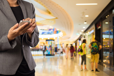 Photo pour Women in shopping mall using mobile phone. - image libre de droit