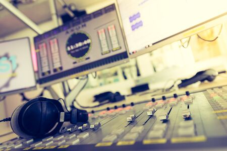 Photo for Close up picture of a soundboard in a broadcasting studio, computers in the blurry background - Royalty Free Image