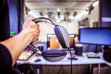 Photo for Young man holds headphones in the recording studio. Buttons, studio, screens and equipment in the blurry background - Royalty Free Image