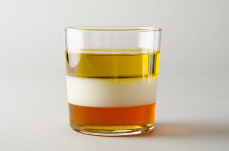 Foto de Physics. Density column. Laboratory glassware containing separed layers of vegetable oil, milk and honey. - Imagen libre de derechos