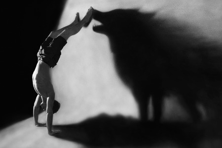 Photo pour Photomanipulation  handstand in studio with wolf shadow - image libre de droit