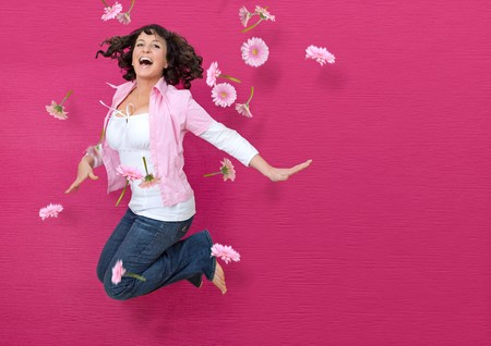 young woman in front of a pink wall jumping through flying flowers