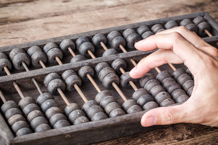 Foto de Vintage tone of Man's hands accounting with old abacus and hold electronic calculator. picture financial concept design. - Imagen libre de derechos