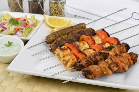 Kebabs - Selection of chicken tikka, paneer tikka and seekh kebabs served with crunchy salad, mint raita and lemon wedges