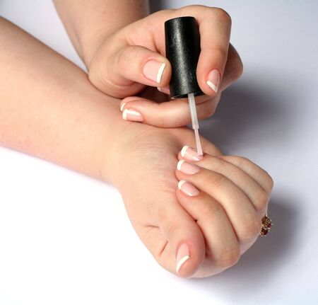 A young woman applies a layer of clear nail varnish over a French polish.