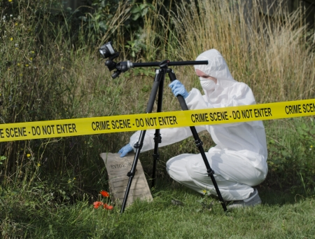 Photo pour Forensic scientist checking for evidence behind a crime scene barrier - image libre de droit