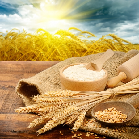 Organic ingredients for bread preparation with golden sunrise on background