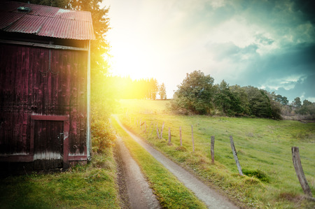 Photo pour Summer landscape with old barn and country road at sunset - image libre de droit