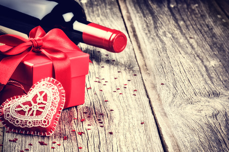 Photo for St Valentine's setting with present and red wine on wooden background - Royalty Free Image