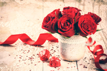 Foto de Valentine's setting with bouquet of red roses and chocolate on old wood background - Imagen libre de derechos