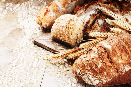 Photo for Freshly baked bread in rustic setting on wooden table - Royalty Free Image