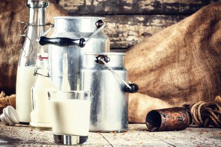 Photo pour Farm setting with fresh milk in various bottles and cans - image libre de droit