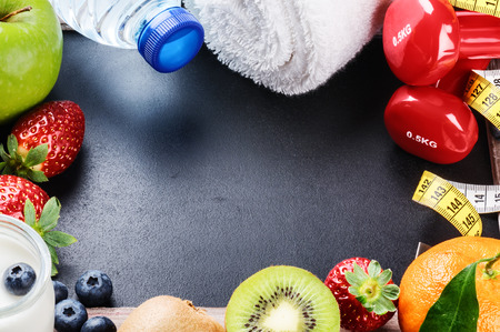 Photo pour Fitness frame with dumbbells, towel and fresh fruits. Copy space - image libre de droit