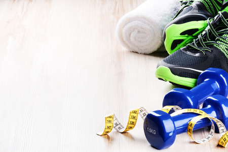 Photo pour Fitness concept with dumbbells,  sneakers and measuring tape - image libre de droit