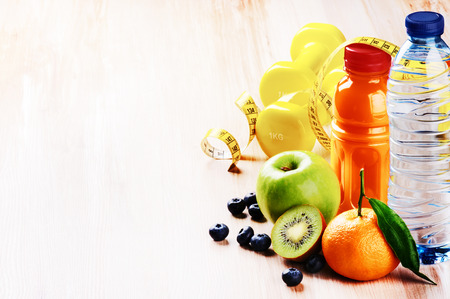 Foto per Fitness concept with dumbbells and fresh fruits. Copy space - Immagine Royalty Free
