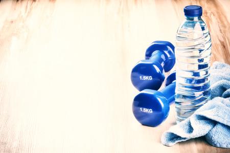 Foto de Fitness concept with dumbbells and water bottle. After workout setting - Imagen libre de derechos