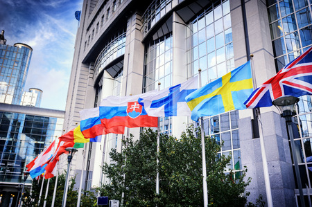 Photo for Waiving flags in front of European Parliament building. Brussels, Belgium - Royalty Free Image