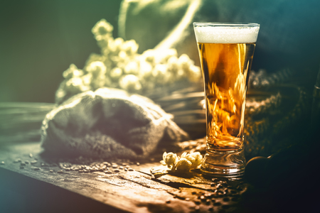 Foto de Glass of fresh cold beer in rustic setting. Food and beverage background with copyspace - Imagen libre de derechos