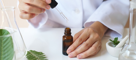Foto de scientist hand pour,drop oil or serum in the laboratory with leaves,equipment,glassware,cosmetic bottle.health and beauty natural organic product concept.herbal medicine. making cosmetic on table. - Imagen libre de derechos