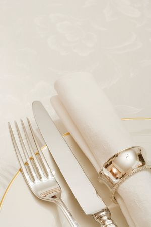 Place setting with cutlery, plate and napkin with copyspace