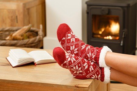 Photo pour Woman in Christmas socks relaxing next to a wood burning stove - image libre de droit