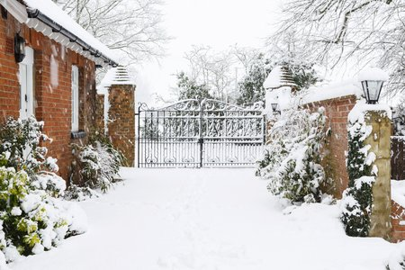 Photo pour Entrance to Victorian house with cast iron gates with driveway covered in snow in winter - image libre de droit