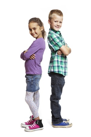 8 year old boy and girl stood back to back on white background