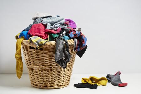 Photo pour Overflowing laundry basket. Household chore concept on white background - image libre de droit