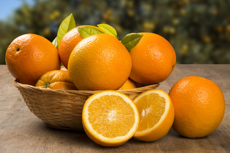 Photo for Close up of some oranges in a basket over a wooden surface. Fresh fruit. - Royalty Free Image