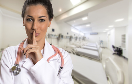 Photo pour Serious doctor woman making silence sign over hospital. - image libre de droit