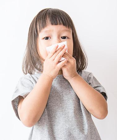 Foto de Cute little asian girl blows her nose over white background (asian) - Imagen libre de derechos