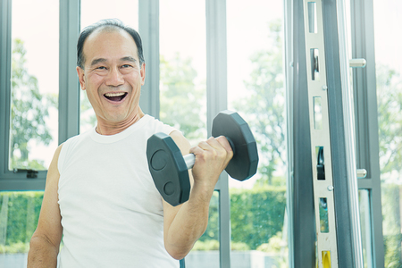 Photo for Asian senior male doing weight training with dumbbells - Royalty Free Image
