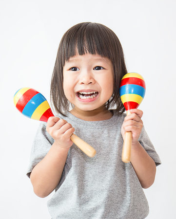 Photo for Little cute asian girl playing the maracas, preschool play group - Royalty Free Image